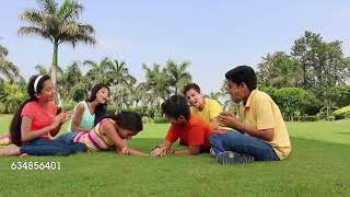Group of teenage boys and girls playing arm wrestling in the park, Delhi, India